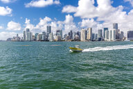 USA, Florida, skyline of Downtown Miami with motorboat on the water - MABF00521
