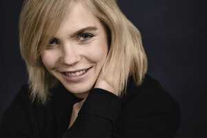 Portrait of smiling blond young woman wearing black pullover - JESF00214