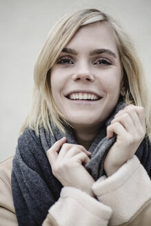 Portrait of smiling blond young woman wearing scarf - JESF00220