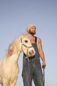 Smiling man with pony under blue sky - KBF00480