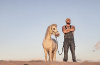 Spain, Tarifa, man with pony standing on the beach - KBF00483