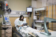 Pregnant woman using digital tablet in hospital room - HEROF09789