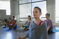 Serene woman meditating in yoga class - HEROF09855