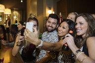 Smiling friends taking selfie at bar - HEROF09888