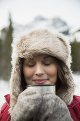 Woman in fur hat drinking hot cocoa outdoors - HEROF09903
