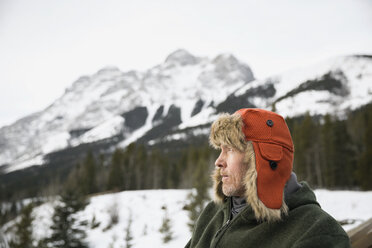 Serious man in fur hat below snowy mountains - HEROF09918