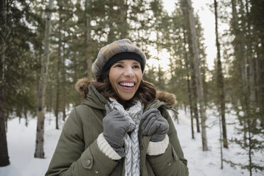 Smiling woman wearing warm clothing in snowy woods - HEROF09921