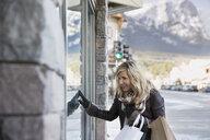 Woman window shopping at storefront - HEROF09951
