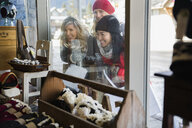 Women in warm clothing window shopping at storefront - HEROF09960