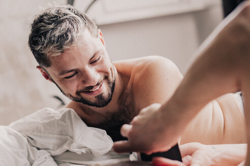 Portrait of smiing gay man with his partner in bed - VWF00049