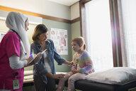 Nurse wearing hijab talking to girl - HEROF10026