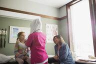 Nurse wearing hijab checking glands of girl - HEROF10032