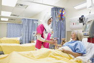 Nurse wearing hijab checking on patient in hospital - HEROF10035