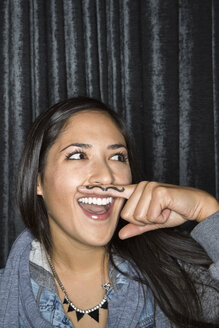 Portrait of playful woman with mustache on finger - HEROF10080