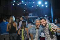 Portrait of smiling men at nightclub - HEROF10140