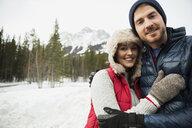 Portrait of hugging couple below snowy mountain - HEROF10146