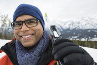 Portrait of smiling man with skis below mountains - HEROF10158