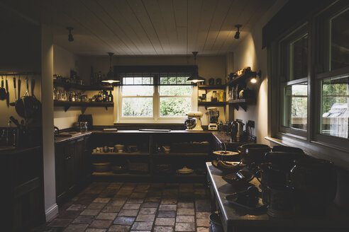 Interior view of kitchen with stone tile floor, wooden ceiling and two sash windows, antique wooden cupboards and wall shelves. - MINF10190