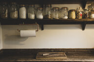 Wooden chopping board and knife on vintage wooden kitchen cupboard, row of glass jars with cooking ingredients on a wooden shelf. - MINF10196