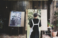 Senior woman wearing black dress and white apron standing in studio, working on painting of trees in forest. - MINF10214