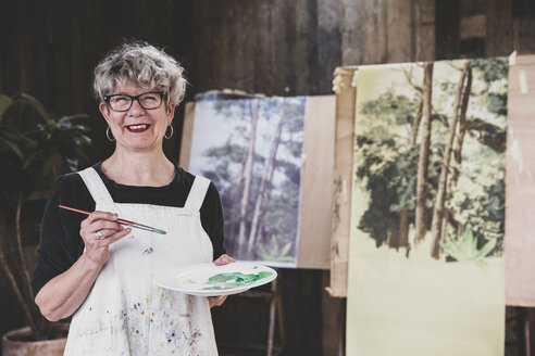 Senior woman wearing glasses, black top and white apron standing in studio, working on painting of trees in forest. - MINF10220