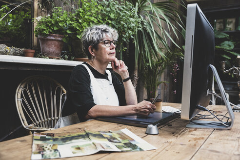 Senior woman wearing glasses, black top and white apron sitting at a wooden table, working on desktop computer. - MINF10223