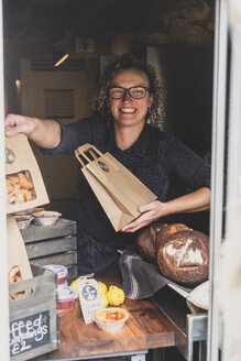 Smiling woman wearing glasses standing in bakery, holding brown paper shopping bag. - MINF10304