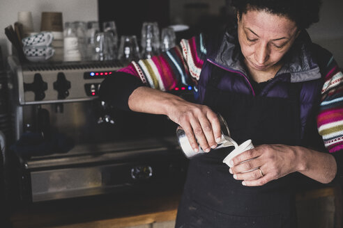 Woman behind espresso machine pouring hot milk into paper cup. - MINF10331