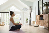 Serene woman meditating at home - HEROF10182