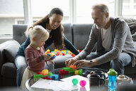 Grandparents and granddaughter playing with plastic blocks in living room - HEROF10250