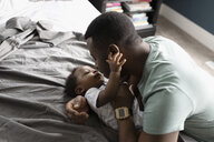 Affectionate father and baby son on bed - HEROF10280