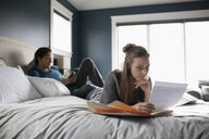 Couple relaxing and working on bed - HEROF10283