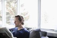 Man reading newspaper in living room - HEROF10292