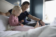 Father watching toddler daughter drawing on digital tablet on bed - HEROF10298