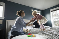 Playful mother and daughter jumping on bed - HEROF10301