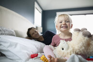 Portrait happy toddler girl playing with stuffed animal on bed - HEROF10307