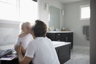 Affectionate, cute toddler daughter kissing father in bathroom - HEROF10313