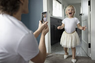 Father with camera phone photographing cute, playful toddler daughter in high heels - HEROF10316