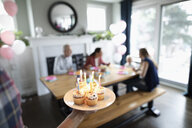 Man serving birthday cupcakes to family in dining room - HEROF10319