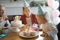Grandparents and toddler granddaughter celebrating birthday, blowing out candles - HEROF10325