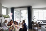 Multi-generation family celebrating toddler daughter s birthday at dining table - HEROF10328
