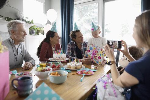 Multi-generation family celebrating toddler girl s birthday at dining table - HEROF10331