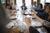 Business people toasting red wine glasses at restaurant table - HEROF10361