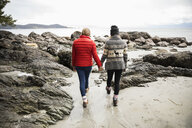 Mother and daughter holding hands, walking on rugged beach - HEROF10387