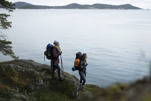 Mother and daughter backpacking on cliff overlooking ocean - HEROF10411