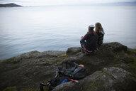 Mother and daughter backpacking, resting on rocks overlooking ocean - HEROF10414