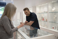 Jewelry boutique business owner helping man at display case - HEROF10417