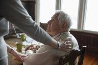 Home caregiver comforting senior man at table - HEROF10435