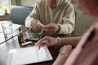 Home caregiver using digital tablet next to senior man with medicinal marijuana - HEROF10438