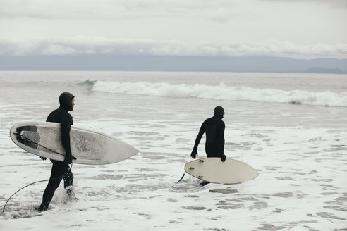 Male surfers in wet suits wading into rugged ocean with surfboards - HEROF10483